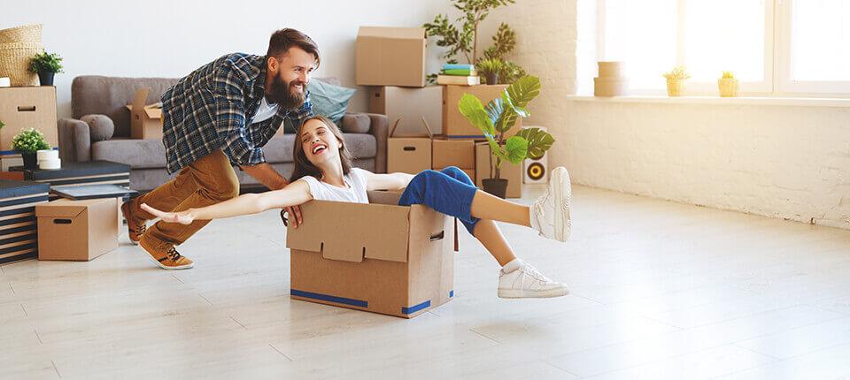 A man pushing a woman in a cardboard box