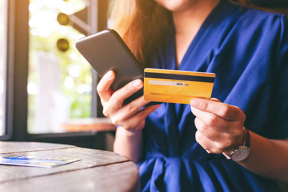 A woman holding a phone and a credit card