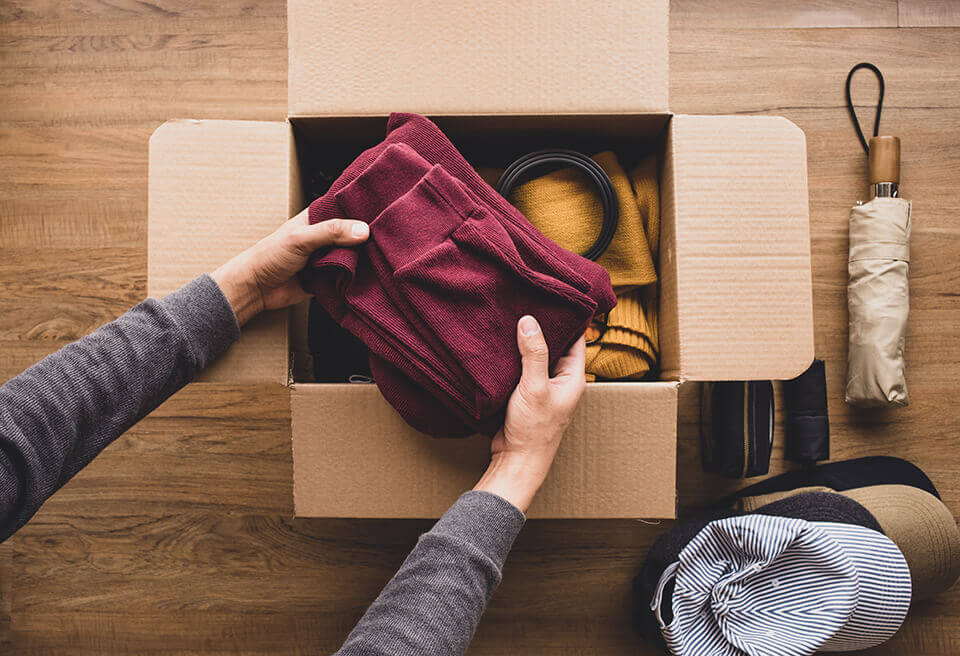 A person placing clothes in a box