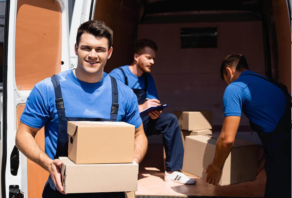 Three men handling boxes