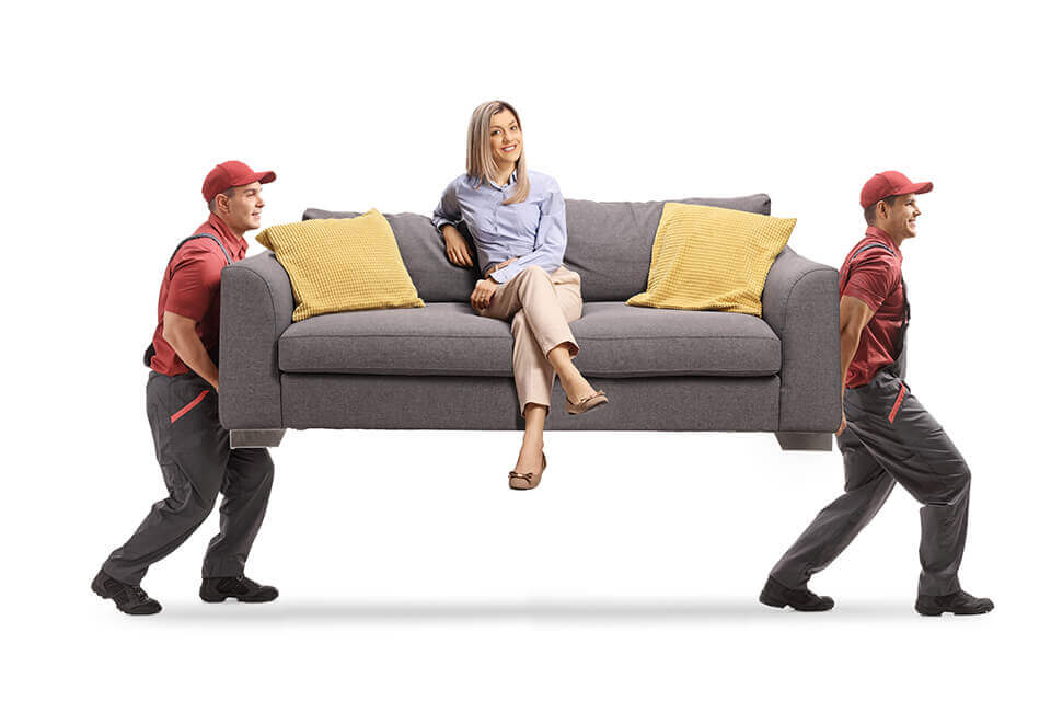 Two men carrying a couch while a woman sits on it