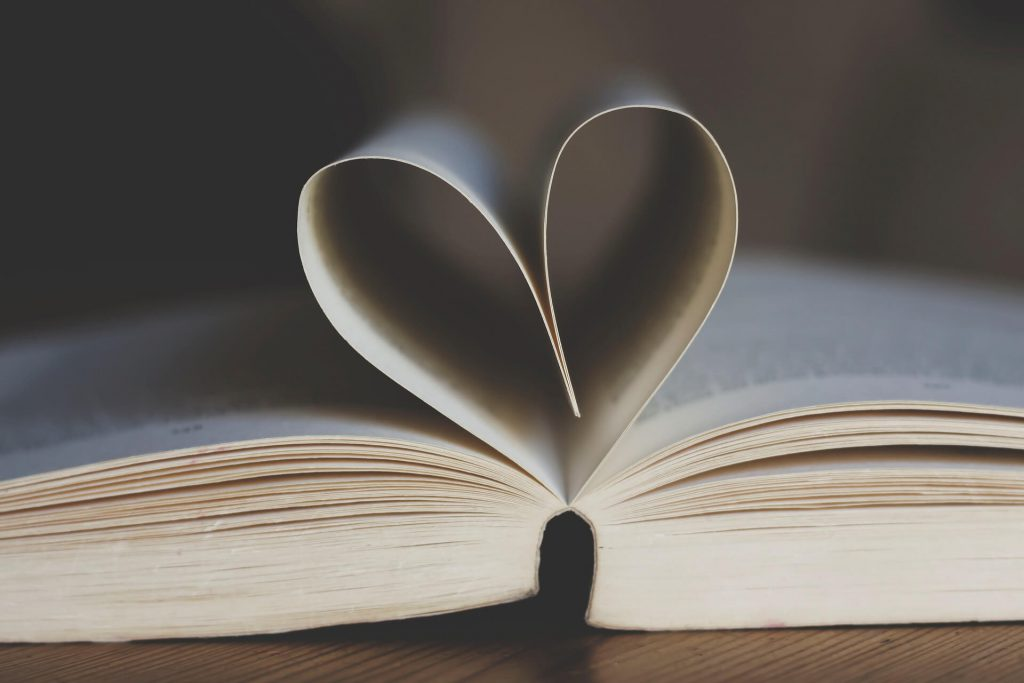 Open paperback publication with pages shaped like a heart
