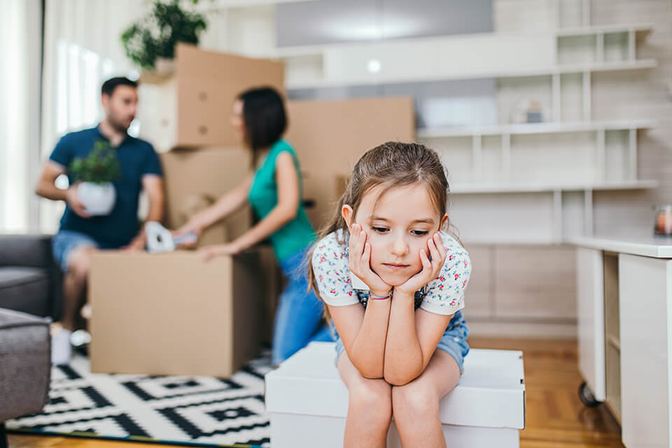 Sad girl sitting on the moving box, parents behind her