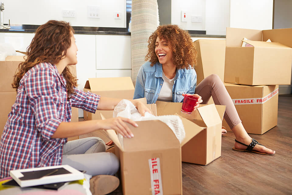 Two women sitting on the floor, surrounded by boxes and laughing