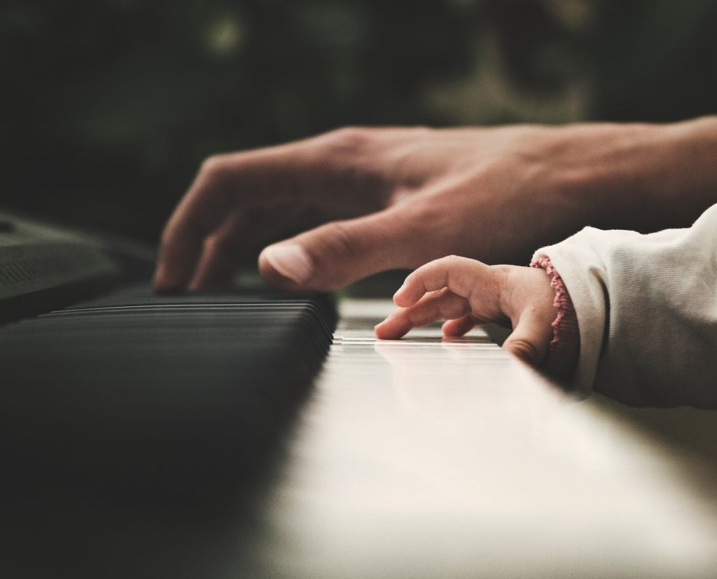 Close look of the baby and man playing the keyboards
