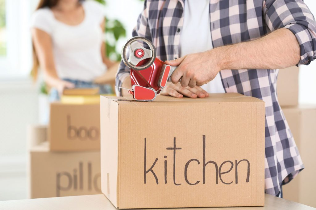 """Man taping a package labeled as """"kitchen"""""""