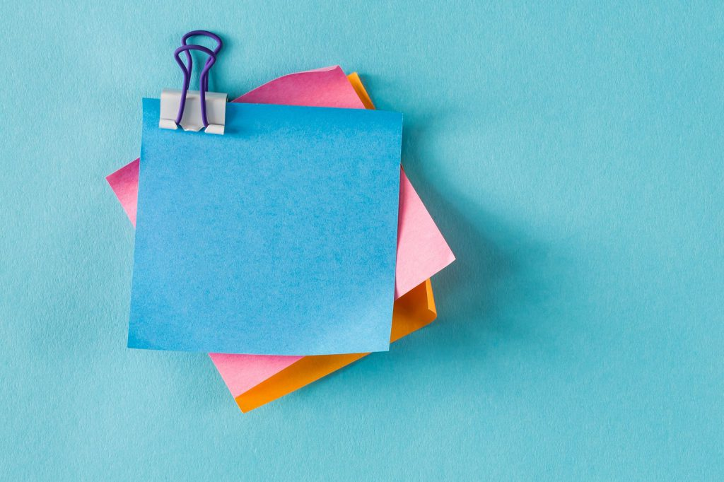 Blue, pink, and orange sticky notes taped to a blue wall