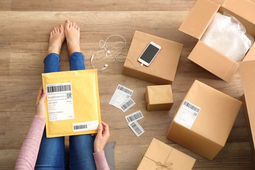 Girl's legs, envelope on them, phone, headphones, and boxes on her right