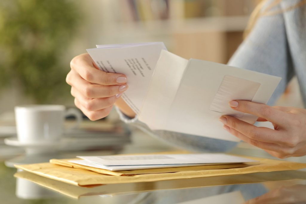 Woman holding an opened envelope, other envelopes on the table in front of her