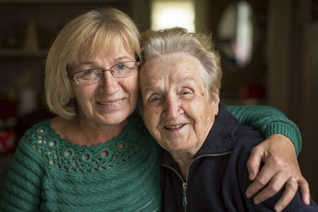 Two older ladies smiling because of the benefits of moving