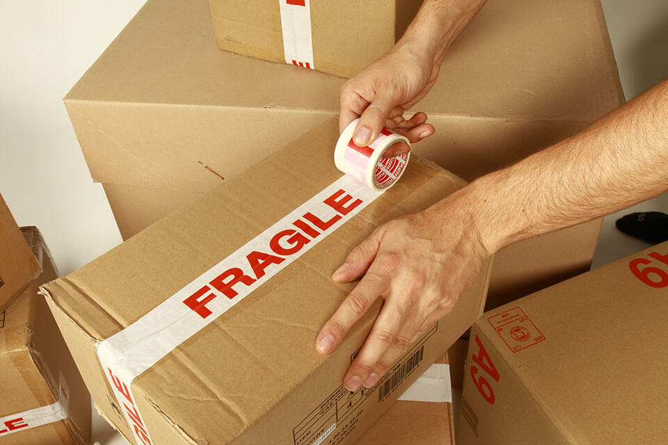 """Man labeling a package with a tape with """"fragile"""" written on it"""