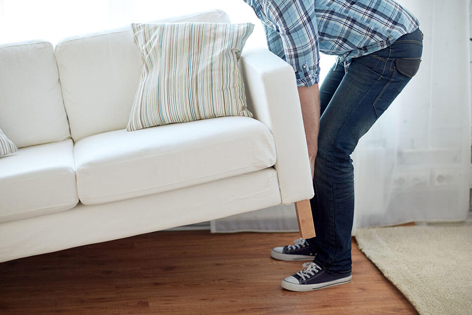 Man lifting the side of the couch