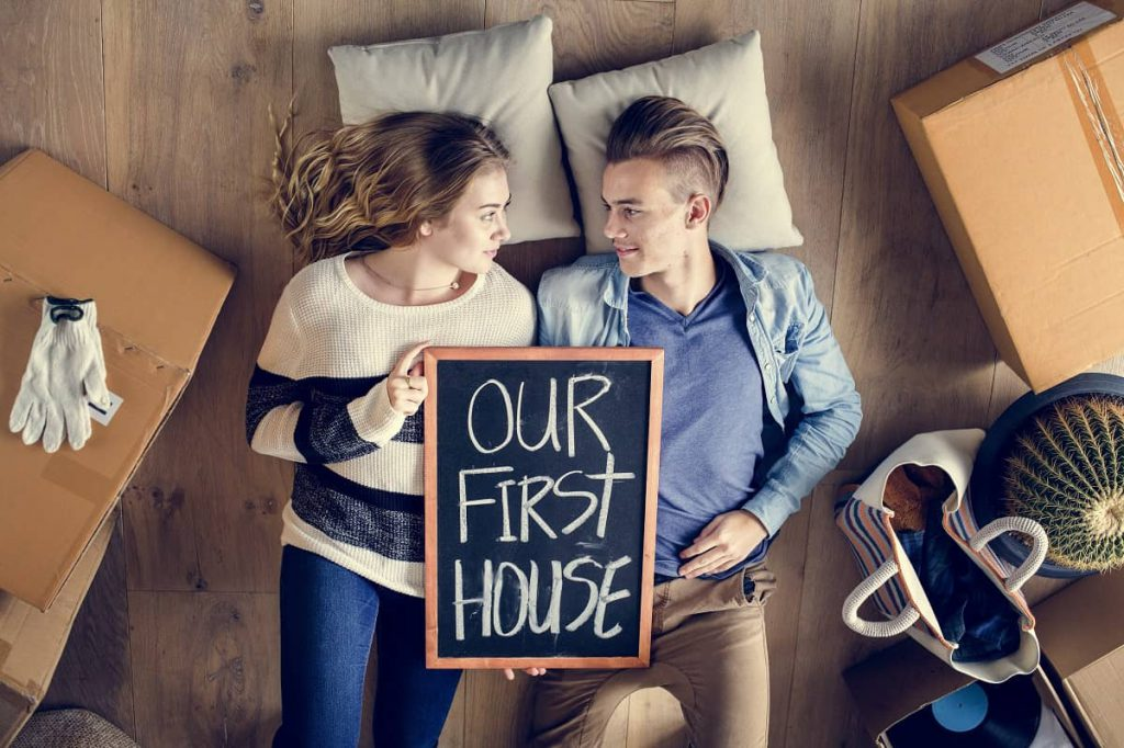 Couple lying on the floor of their first apartment