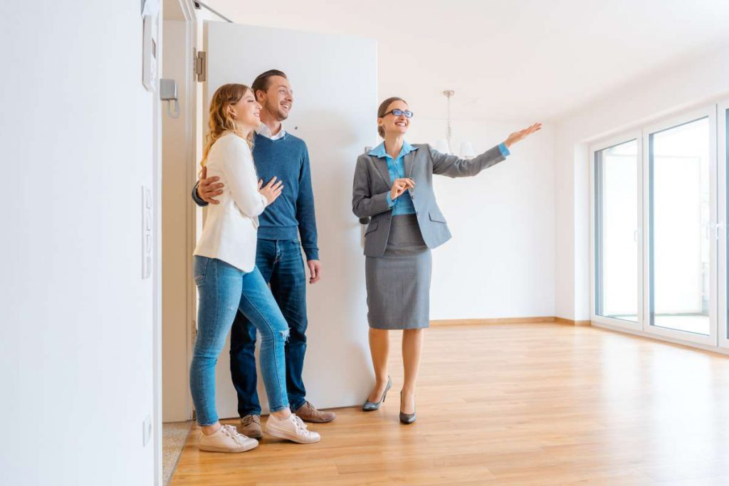 Three people looking at an apartment with a realtor