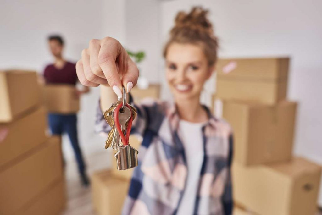 A girl holding keys from the home to which professional movers in Chicago will soon move her
