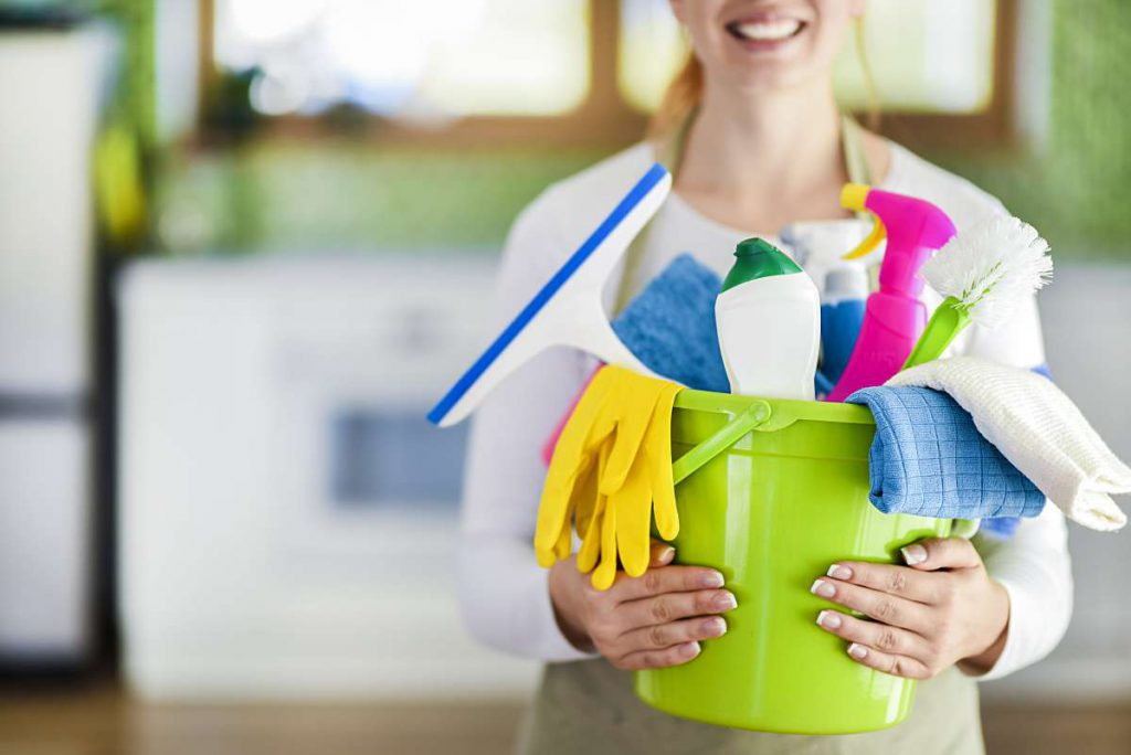 Person holding bucket with different supplies