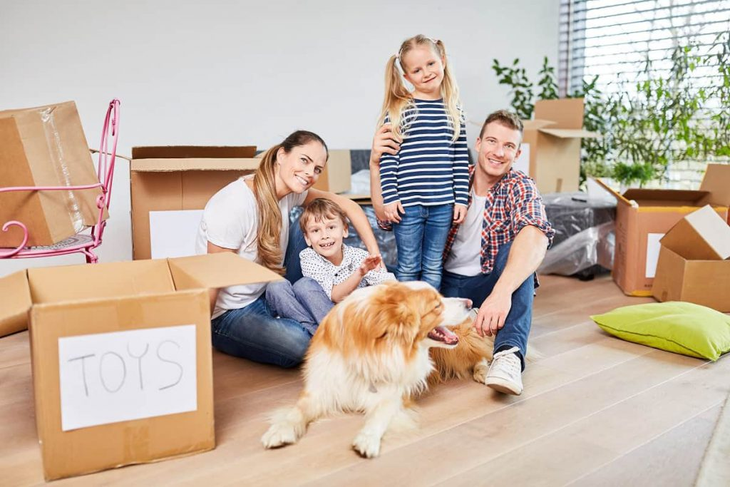 Man, woman, two kids, and a dog surrounded by packages before the move with professional movers in Chicago