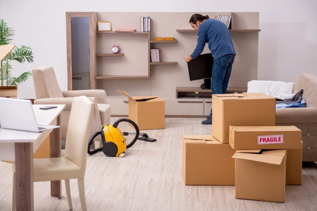 Man picking up a TV from the shelf in a room full of packages