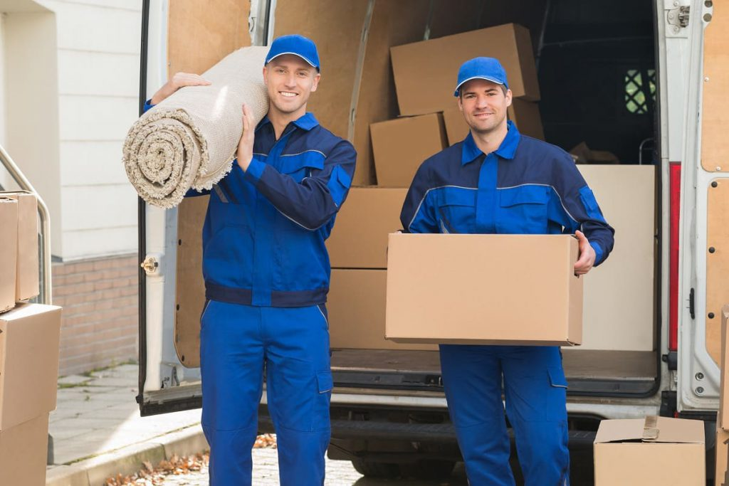 A mover in Chicago, IL, carrying a package and another one holding a carpet
