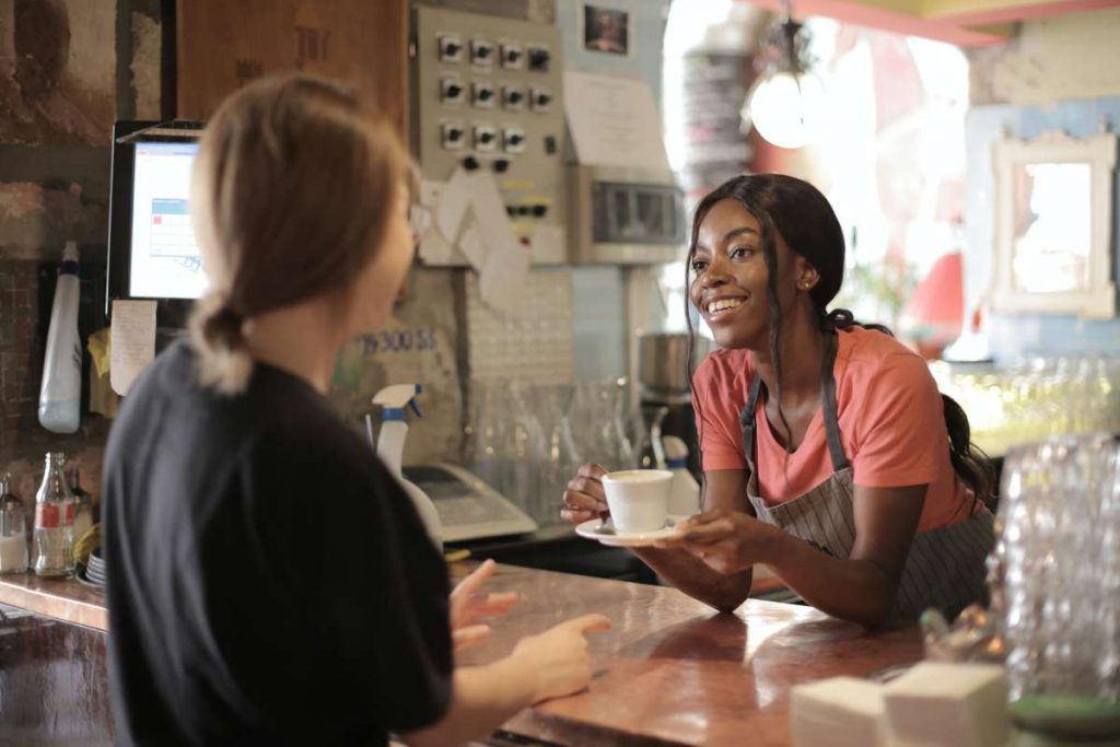 A girl serving coffee to woman hiring the best moving services in Chicago