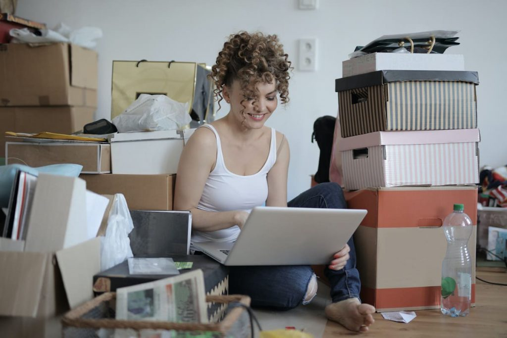 Woman looking at the laptop, surrounded by packages, waiting for Chicago movers
