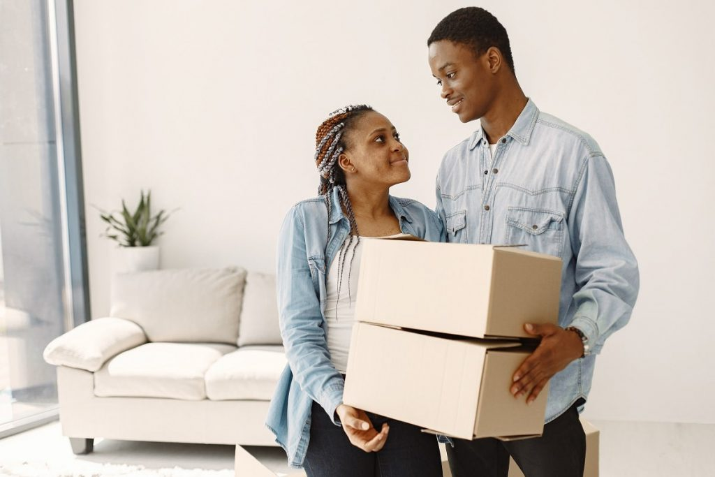 Couple bringing boxes inside the home